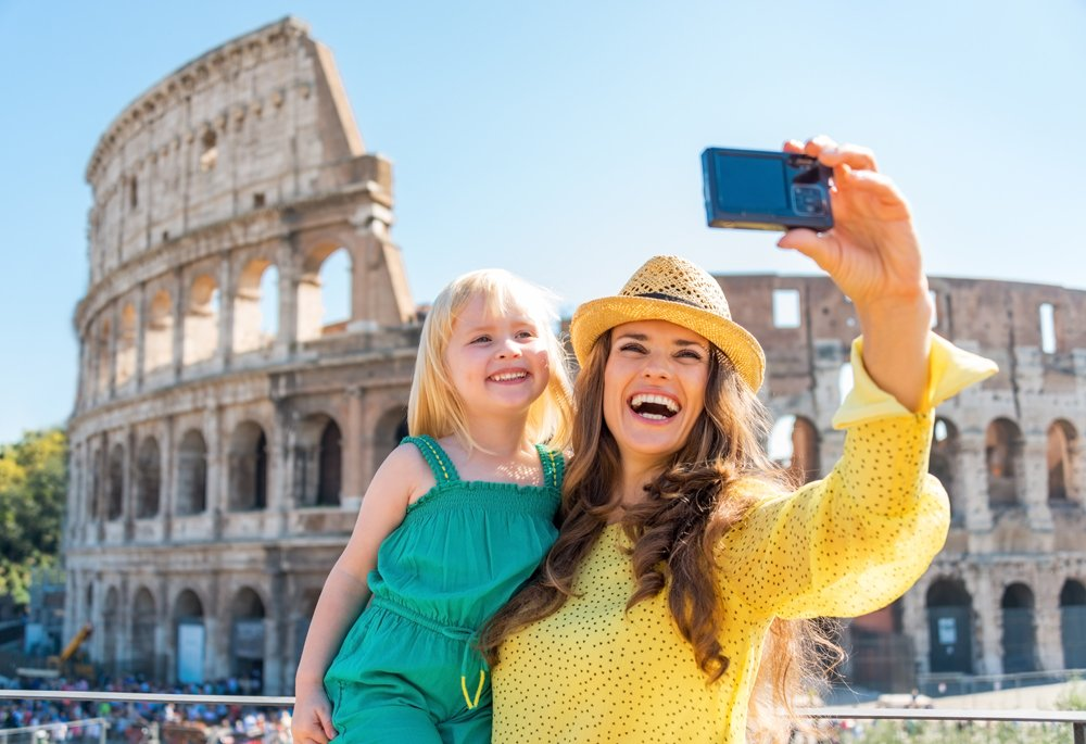 Mother and baby girl taking selfie in front of Colosseum in Rome, Italy