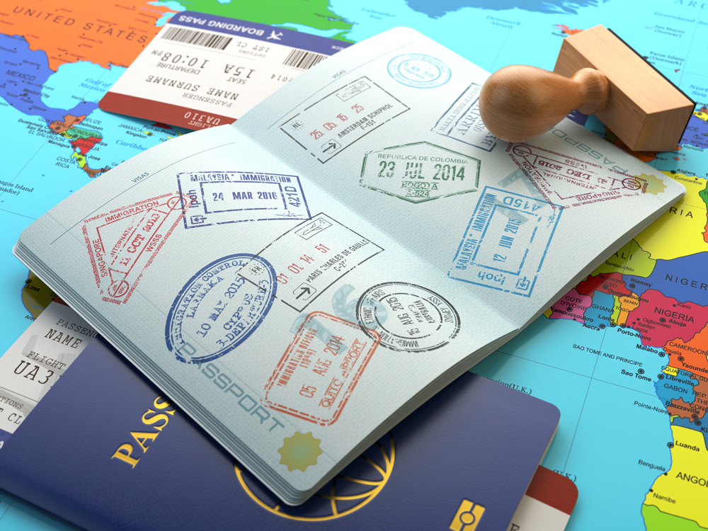 Opened passport with stamps, airline boarding pass tickets and stamper on world map