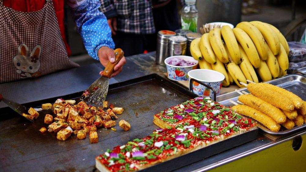 Street food vendor cooking spicy fried tofu in Muslim Quarter, Xian, China