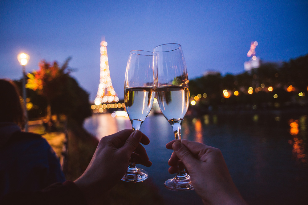Two hands with champagne glasses in front of Eiffel Tower in Paris, France