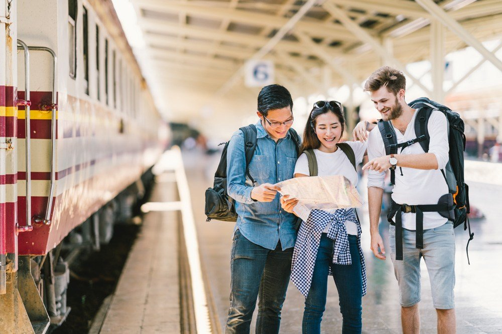 Young travellers using local map to navigate at train station platform, Asia