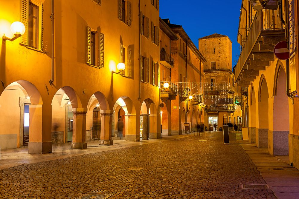 Evening view of a narrow cobblestone street in town of Alba in Piedmont, Italy