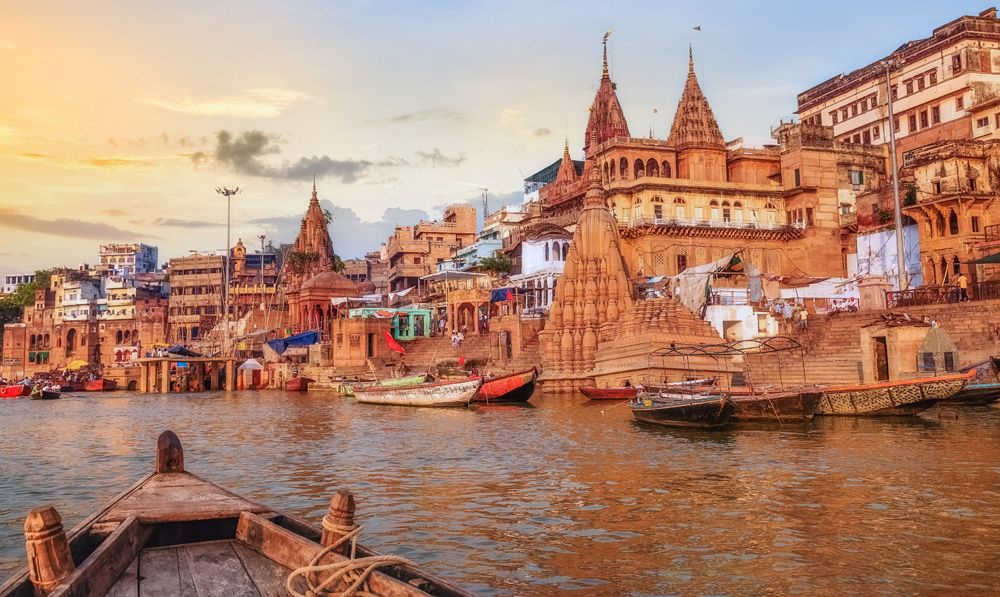 Ganges River ghat with ancient city architecture as viewed from a boat on the river at sunset, Varanasi, India