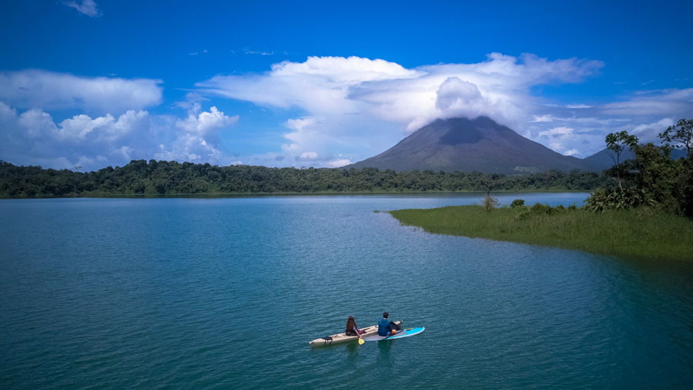 Couple paddling at Arenal Lake and admiring Arenal Volcano, Costa Rica