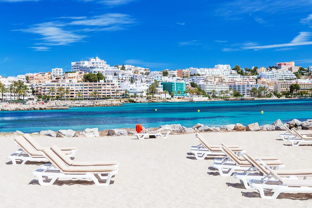 Sunbeds and city view on a beautiful beach in Ibiza, Balearic Islands, Spain