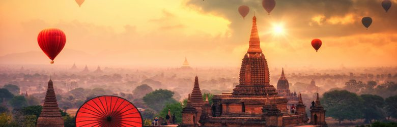 Burmese woman holding traditional red umbrella looking at Hot air balloon over Bagan in misty morning, Myanmar
