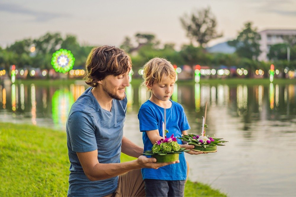 Father and son tourists celebrating Loy Krathong, Thailand