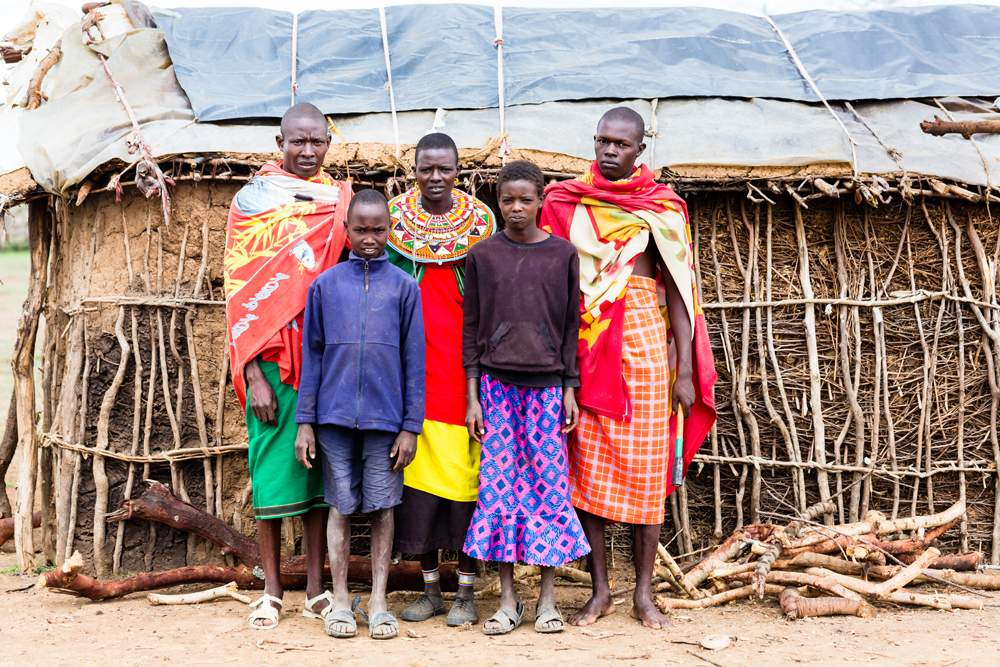 Maasai family posing in front of hut, Kenya