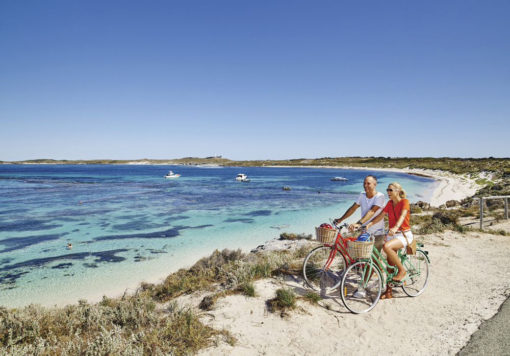 Couple with bikes at Salmon Bay, Rottnest Island, Australia - Tourism Western Australia
