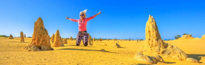 Blond girl jumping in the Pinnacles desert of Nambung National Park, Western Australia, Australia