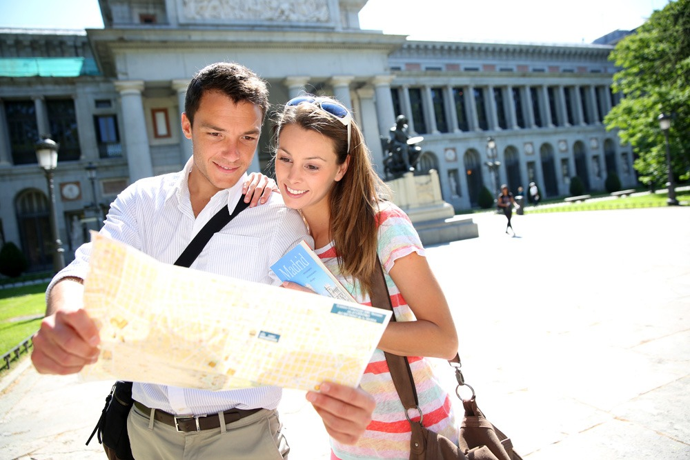 Couple reading city map in front of Prado museum, Madrid, Spain