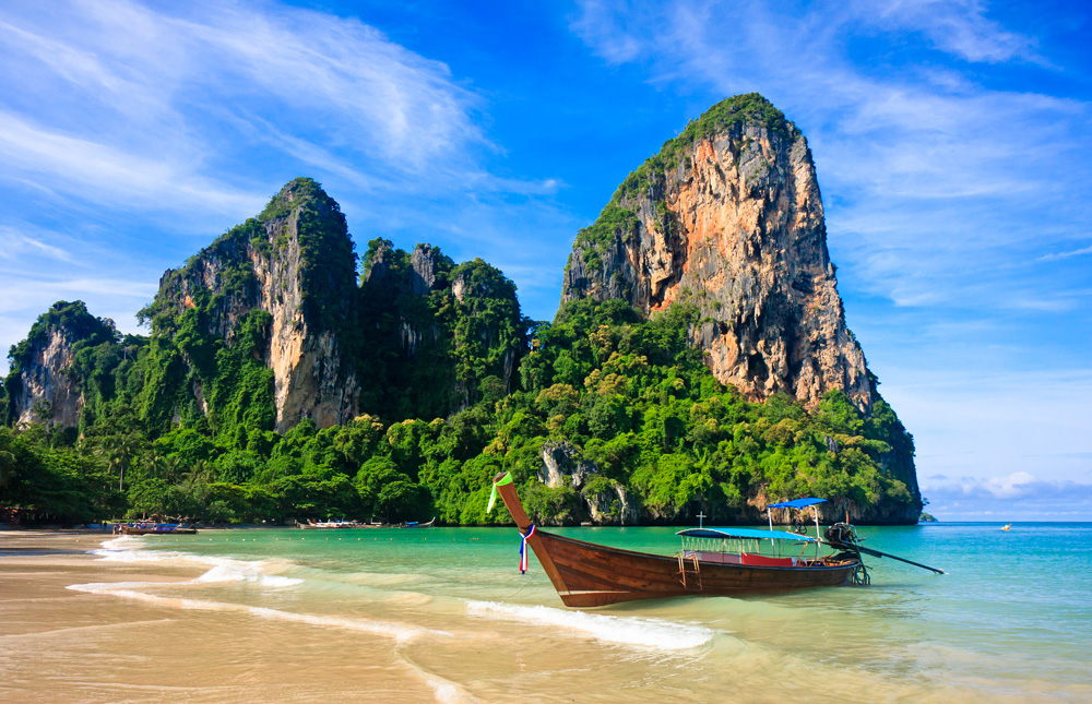 Limestone cliff and longtail boat at Railay Beach in Krabi, Thailand