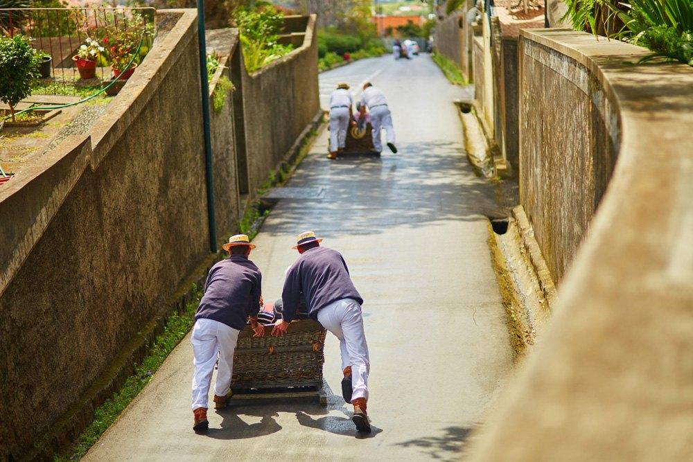Toboggan runners pushing toboggans in Funchal, Madeira island, Portugal