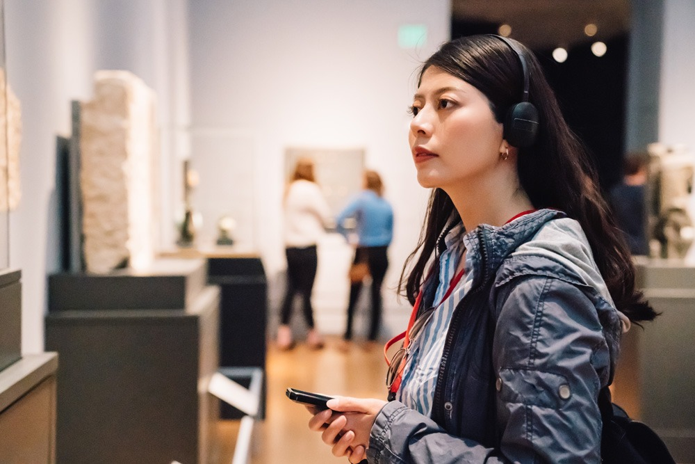 Woman at a museum exhibition, listening to the voice guide