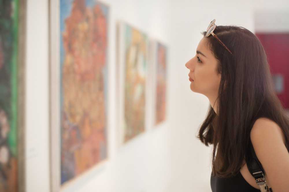 Young woman looking at modern painting in art gallery or museum