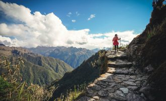 Female hiker walking towards Machu Picchu on the famous Inca Trail, Sacred Valley, Peru