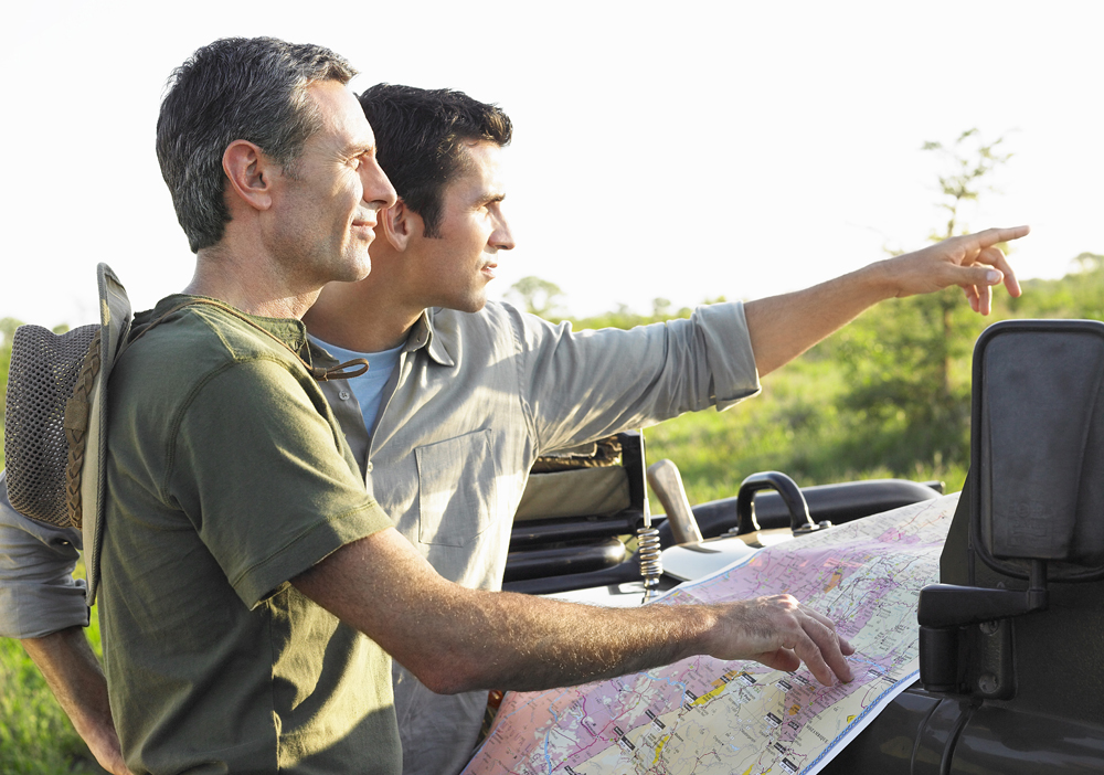 Two male friends with map on bonnet of jeep, Africa