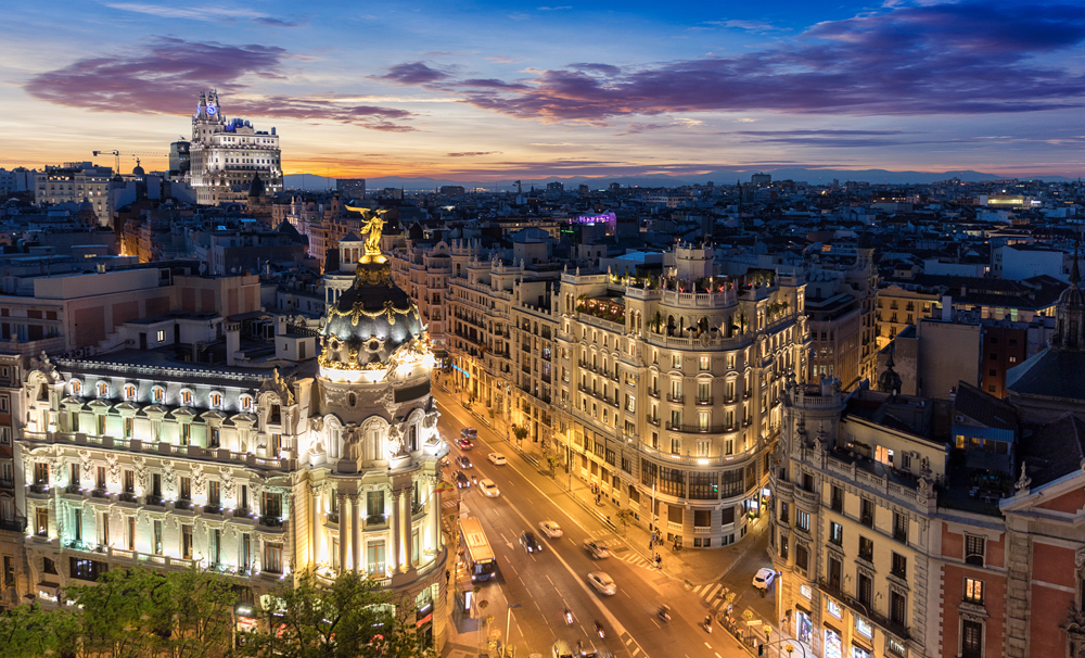 View of the Metropolis Building and Gran Via from Circulo de Bellas Artes rooftop at sunset, Madrid, Spain