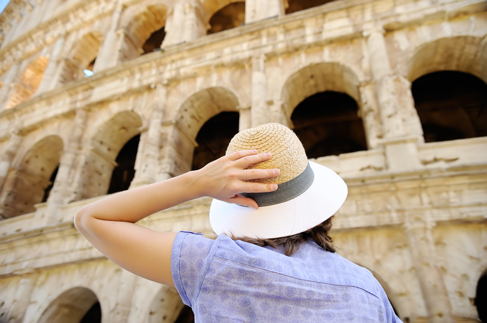 Young female traveller looking at the Colosseum in Rome, Italy