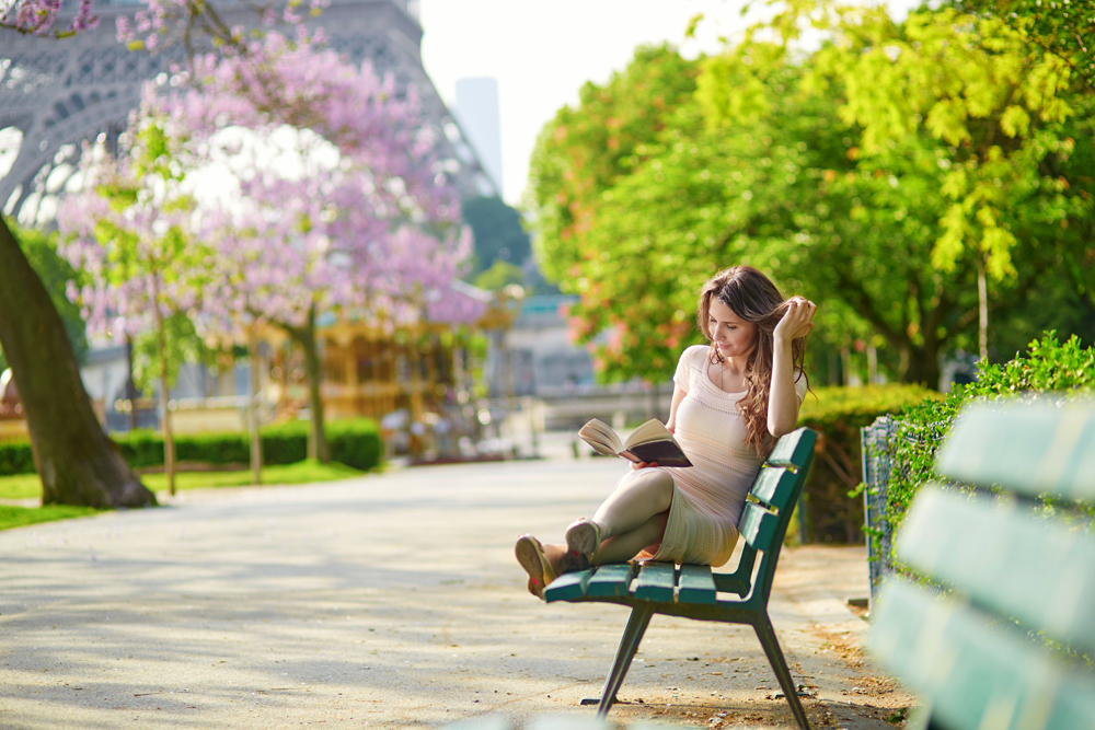 Young woman near the Eiffel Tower, reading on a bench, Paris, France