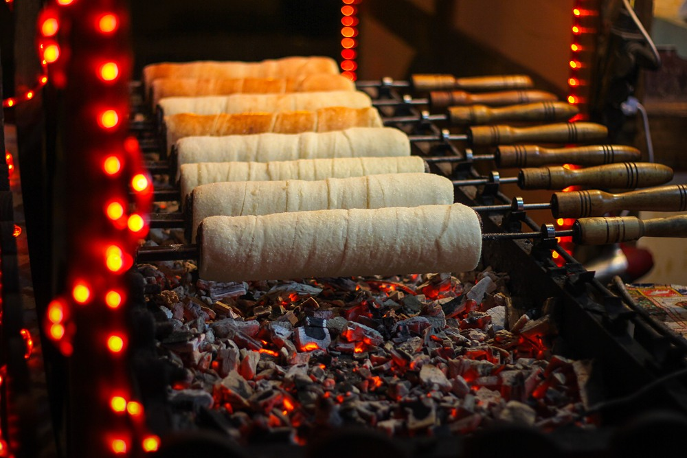Chimney cakes baking over hot coals at a Christmas market stand in Budapest, Hungary