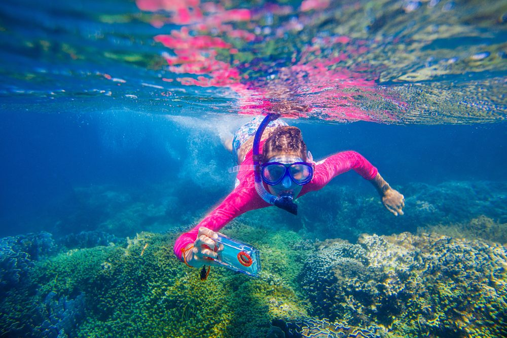 Girl taking pic underwater with waterproof camera