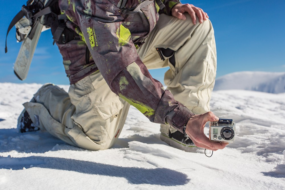 Man filming with GoPro camera in snowy mountain range