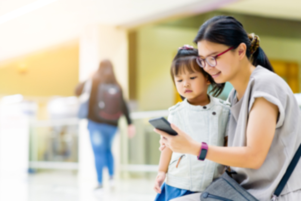 Mother and daughter in airport looking at smartphone
