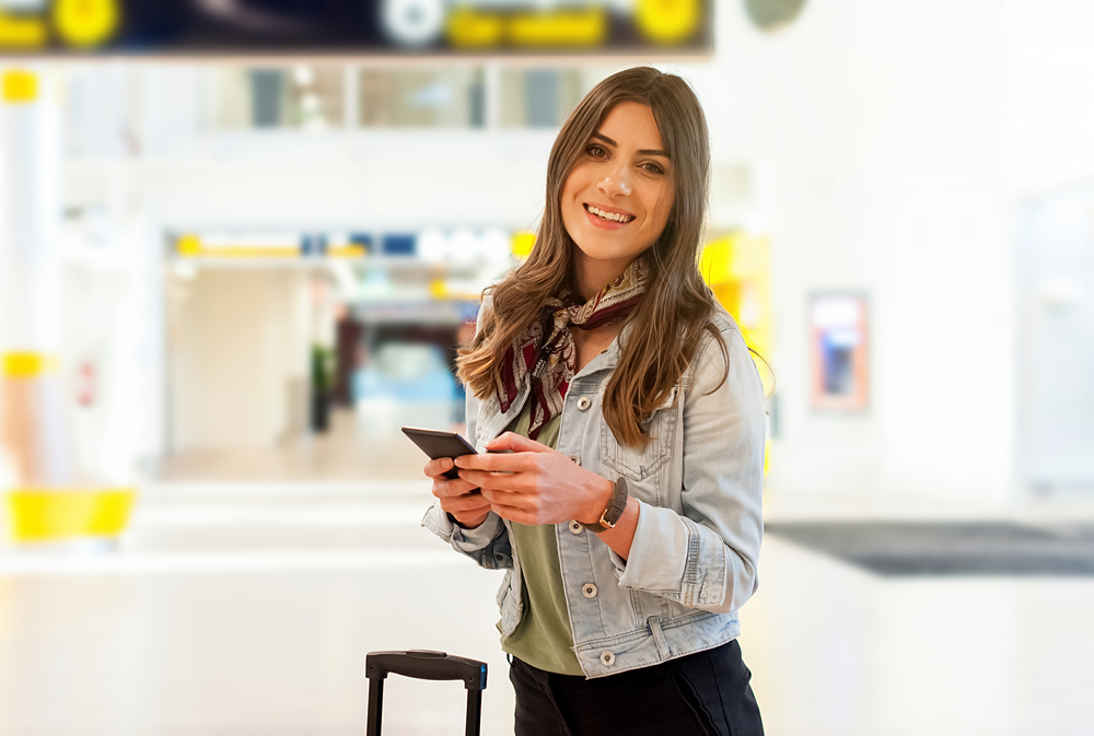 Smiling young woman at the airport with trolley bag, holding a smartphone