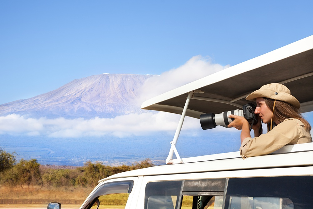 Woman taking shots during Kenyan safari game drive
