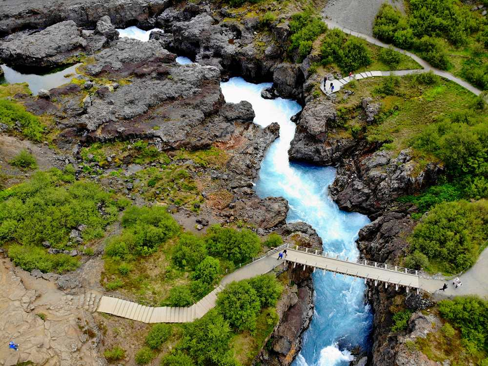 Aerial view of the milky blue river and a bridge near Barnafoss Falls, Iceland