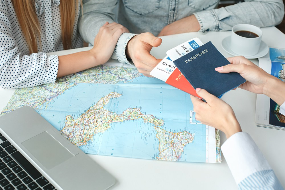 Couple in a tour agency with tickets and passports