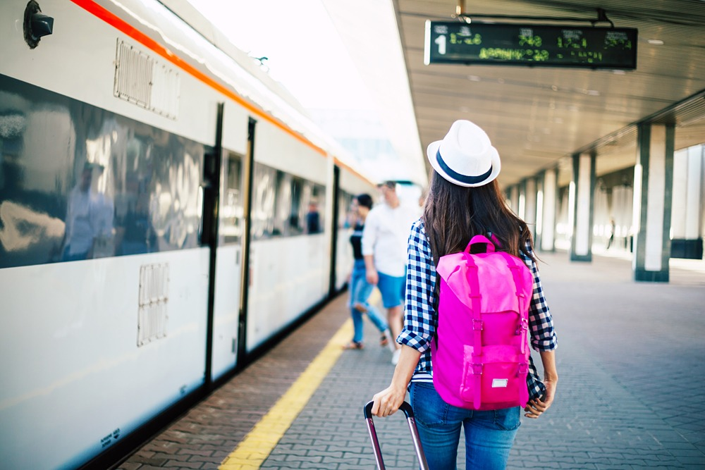 Female tourist with backpack and suitcase waiting for train on railway station