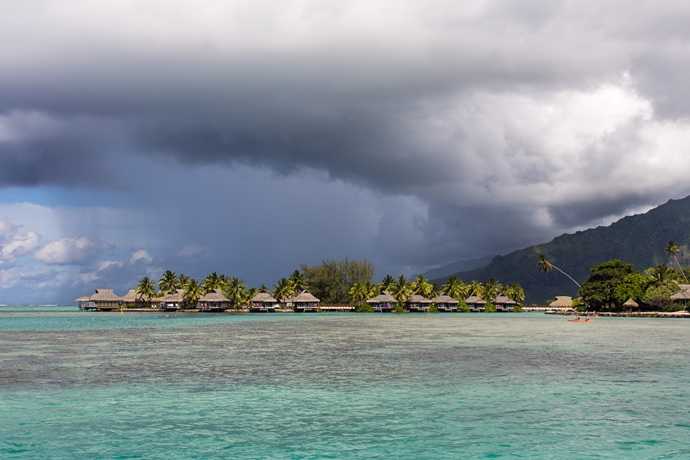 Overwater bungalows and a stormy sky and huge rain cloud, Tahiti (French Polynesia)