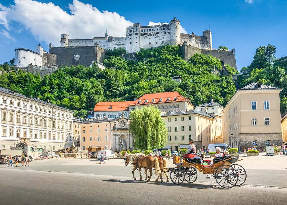 Panoramic view of Salzburg with traditional horse-drawn Fiaker carriage and Hohensalzburg Fortress, Austria