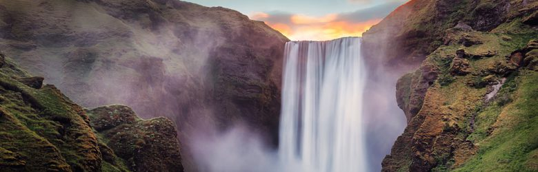 Skogafoss waterfall with colourful sky during sunset and Skoga river, Iceland