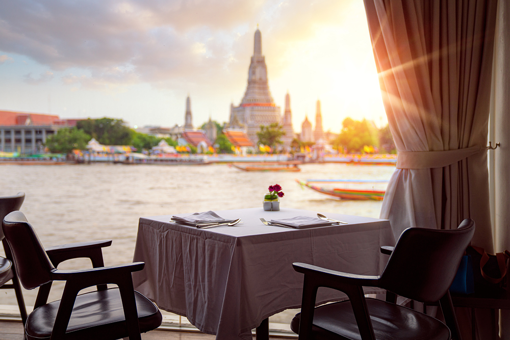 View of Wat Arun (Temple of Dawn), from riverside bar in Bangkok, Thailand