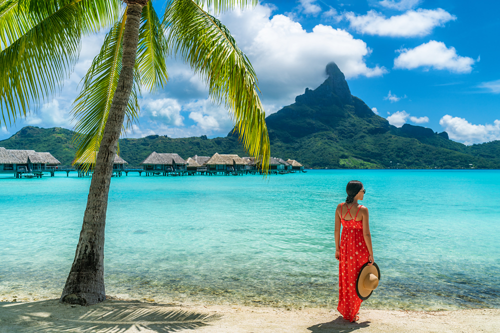 Woman on beach with view of Mt Otemanu in Bora Bora, Tahiti (French Polynesia)