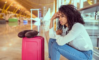 Woman sad and unhappy at the airport with flight cancelled